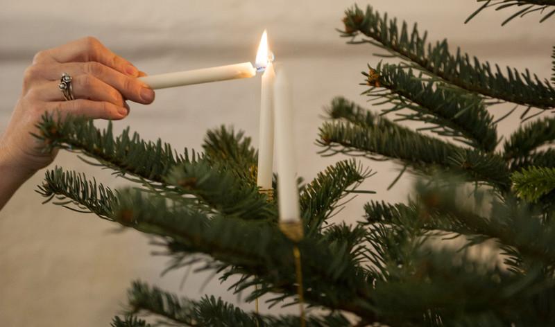Lys tændes på juletræ i en kirke