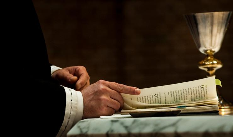 Præst ved alteret med liturgibog