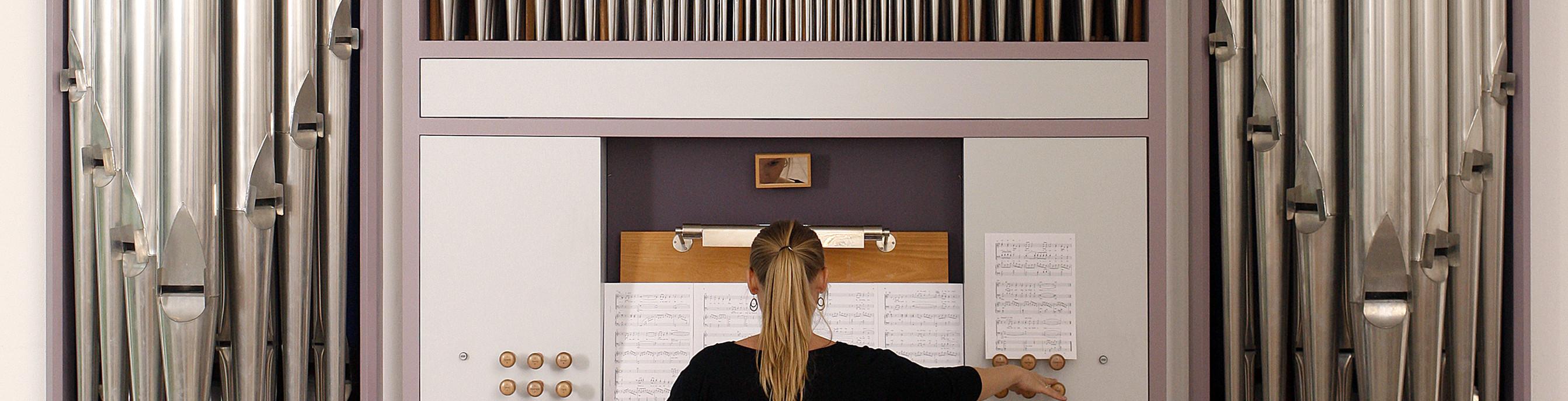 Billede af organist ved orgel bagfra