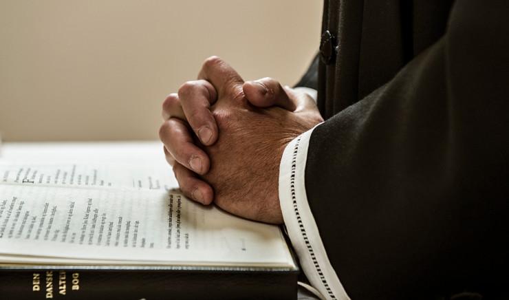 Foldede hænder på liturgibog