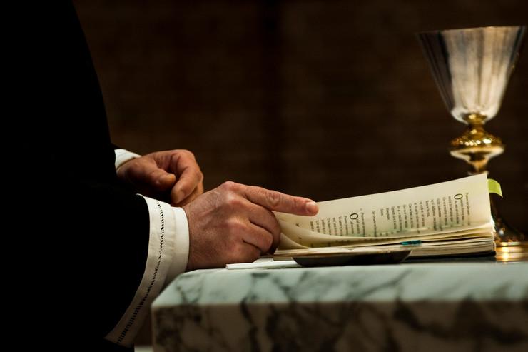 Præst med bog ved alteret